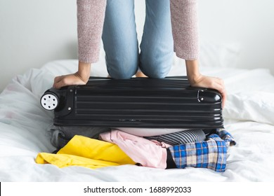young girl headache with overload suitcase packed because too many things in the luggage.