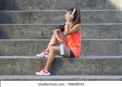 Young girl with headphones and bottle of water sitting at the stairs and relax after jogging