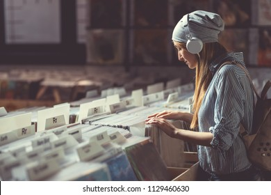 Young girl with headphones browsing records in a music store