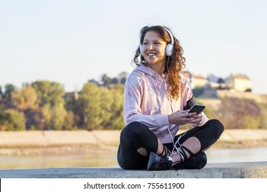 Young girl with headphones on her head listening music and relax after jogging