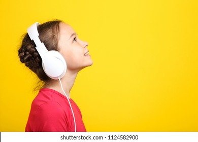 Young girl with headphones on yellow background