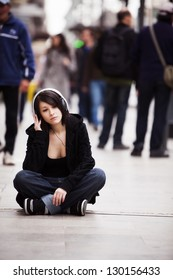 Young girl with headphones sitting on sidewalk