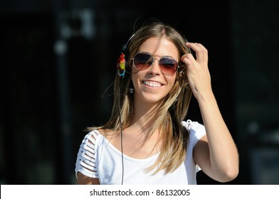 Young girl with headphones and sunglasses dancing in the street