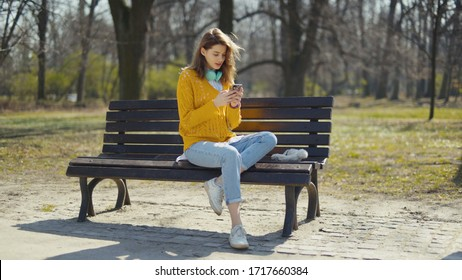 Young girl with headphones using phone in a city park.