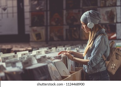 Young girl with headphones in a vinyl store