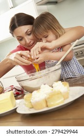 Young Girl Helping Mother To Bake Cakes In Kitchen