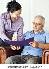 young girl helps a mature man with a form