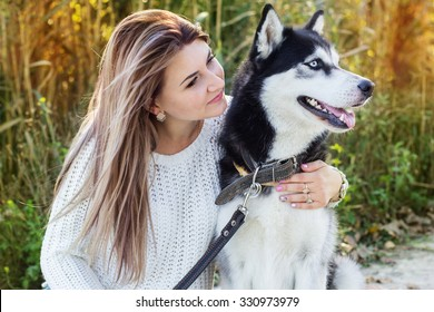 Young girl and her blueyed dog husky is lying outdoors in a park near lake in autumn time
