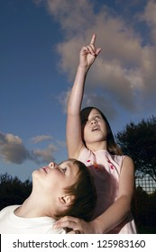 Young girl and her brother looking up into the heavens as she points out something of interest to him