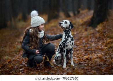 Young girl with her Dalmatian dogs in an autumn park