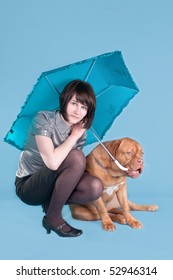 Young girl and her dog both holding un umbrella