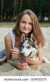 Young girl and her dog (husky) walking in autumn in a city park. Training the dog