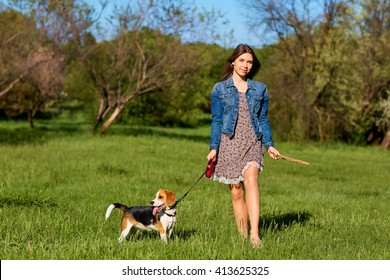 Young girl with her dog playing in the park.