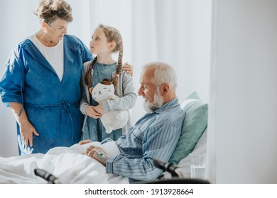 Young girl and her grandmother visiting sick grandfather in a hospital bed