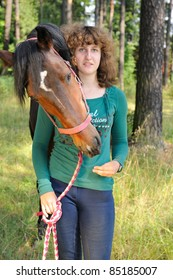 Young girl and her horse nearby. Horse hugs its owner. Girl looks at camera.