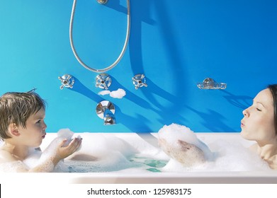 A young girl and her little brother sitting up to their necks in bubbles in the bath have fun blowing bubbles at each other off their cupped hands