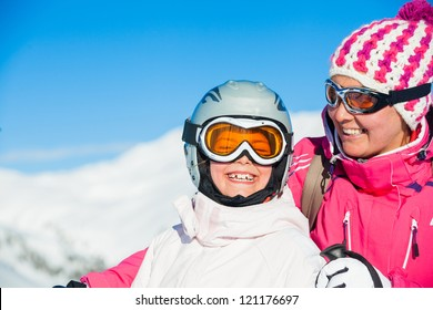 Young girl with her mother a ski outfit jumping in snow at winter outdoor in the Tirol, Austria