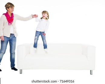 Young girl with her mother in a sofa isolated on white background