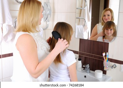 A young girl and her mother take care of the hair in his bathroom
