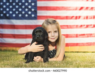 Young girl with her puppy in front of American flag