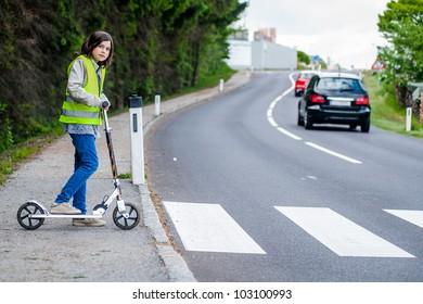 Junge Mädchen mit ihrem Roller wird auf die Kreuzung gehen