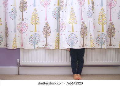 Young girl hiding behind a curtain with only her legs showing