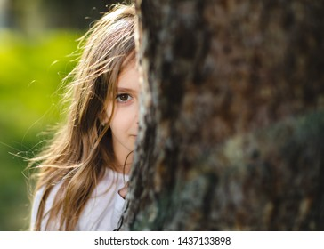 Young girl hiding behind the tree. Portrait of young girl behind the tree in park. Half face of girl behind tree.