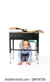 young girl hiding under her school desk