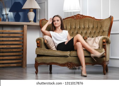 young girl in high heels sitting on the sofa, in the room
