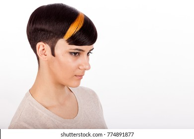 Young girl with highlighted bicolor masculine pixie short haircut. Horizontal studio portrait with negative space.  White background.