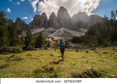 Young girl hiker with the back at the camera looking towards the cliffs in Dolomites, Italy. Beautiful landscape scenery.