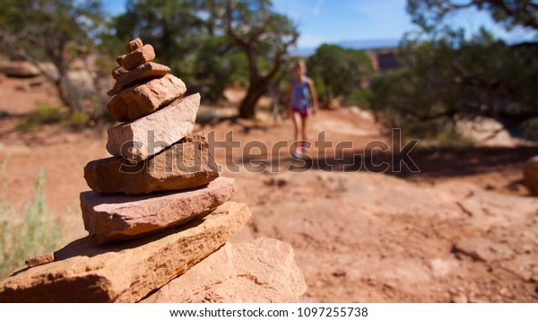 A young girl hikes in the background past a cairn on a desert trail in the Colorado National Monument near Fruita, Colorado.