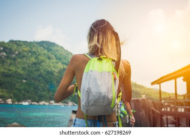 Young girl hiking near the sea at sunset