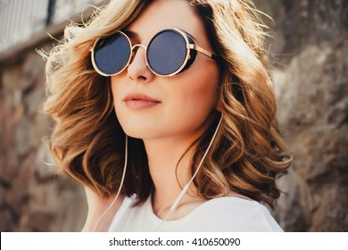 Young girl hipster posing in the street listening music, outdoor fashion portrait, headphones mp3 player, sunglasses, street style, red lips make up, hair, tan, cute, celebrities