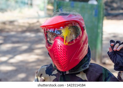 Young girl was hit in the face by bullet on the paintball playground in the forest. She has red safety helmet fatigues and red gun full of yellow bullet.