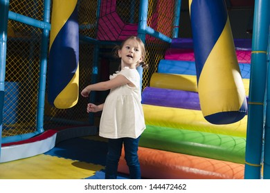 Young girl hitting foam object in play gym