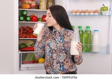 Young girl hold bottle of milk, standing near the open fridge in the kitchen