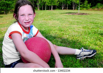 Young girl holding ball looking hot, sweaty and tired after vigorous play