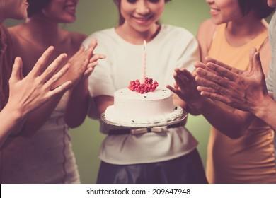 Young girl holding birthday cake