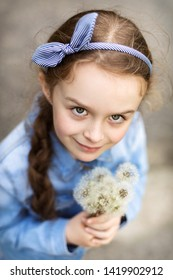 Young girl holding  bouquet  of overblown dandeilions