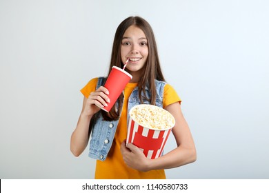 Young girl holding bucket with popcorn and paper cup on grey background