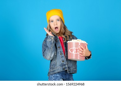 Young girl holding bucket with popcorn on blue background