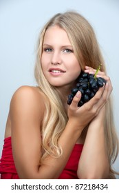 Young girl holding a bunch of grapes