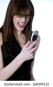 Young girl holding a cell phone and looking at the screen with  angry expression on her face