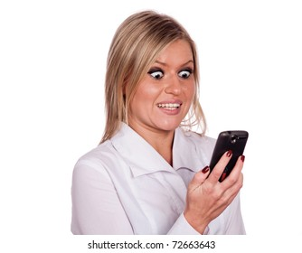 The young girl is holding a cell phone and looking at the screen with a surprised expression