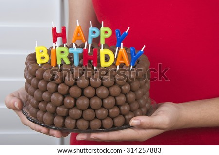 Young Girl Holding Chocolate Birthday Cake Decorated With Candy Malt Balls In Front Of Her