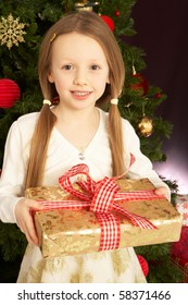 Young Girl Holding Christmas Present In Front Of Christmas Tree