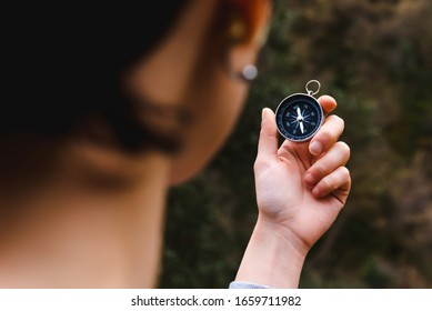 young girl holding a compass in hand, ready to travel, keep calm. Tourism, traveling, hiking and healthy lifestyle concept.