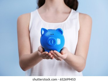 Young girl holding cute piggy bank in hands on light background. Saving for education concept