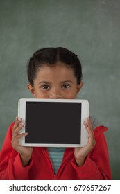 Young girl holding digital tablet in front of her face against chalk board